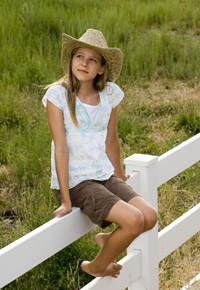 cowgirl sitting on fence