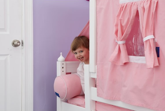 little girl peeking out of maxtrix toddler bed
