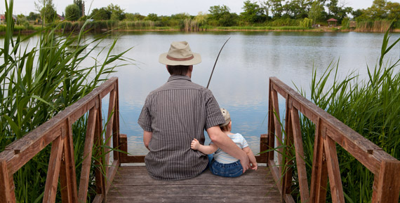 father and son fishing in pond