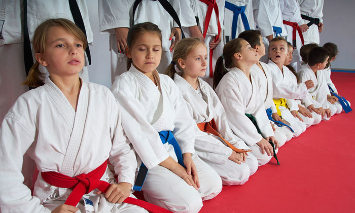 martial arts students sitting in row on gym floor