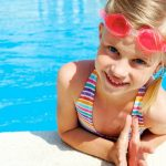 little goggle girl swimmer smiling into camera