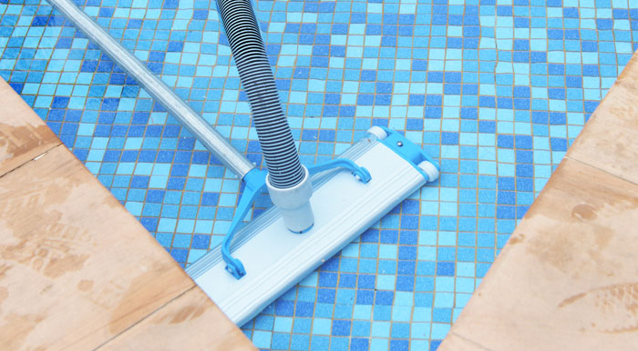 vacuuming bottom floor of swimming pool