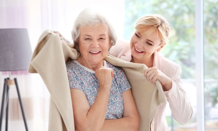 friendly young woman wrapping elderly lady with warm blanket