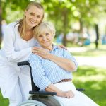 nurse caring for elderly lady in wheelchair