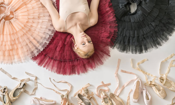 ballerina lying on floor surrounded by tutus and shoes
