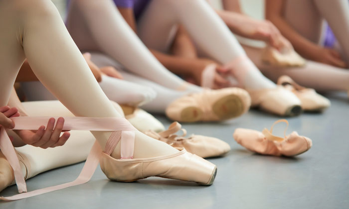 ballerinas putting on their lace ballet shoes