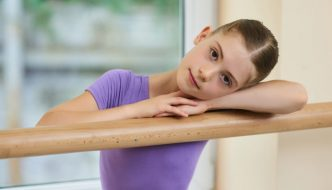 beautiful young ballerina girl resting arms head on barre