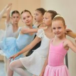 beautiful young ballerina girls resting against barre