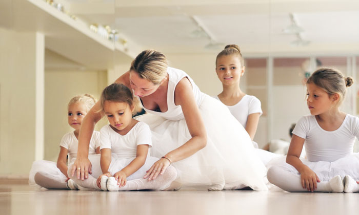 dance teacher helping young ballerina girl get positioned