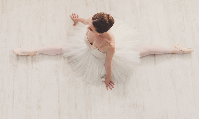 looking down on ballerina legs stretched out on floor