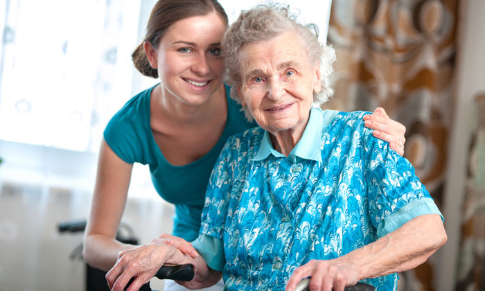 young adult girl kindly assisting elderly lady