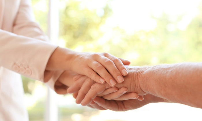 young woman grasping hands of elderly person