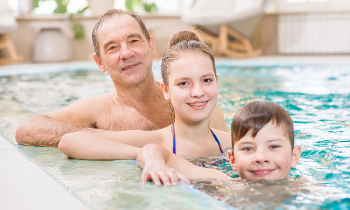 father with daughter and son in pool water