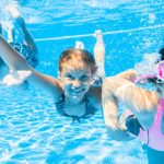 three kids swimming happily underwater