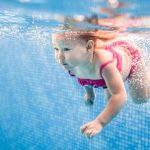 toddler girl underwater in pool