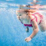 toddler girl underwater in pool