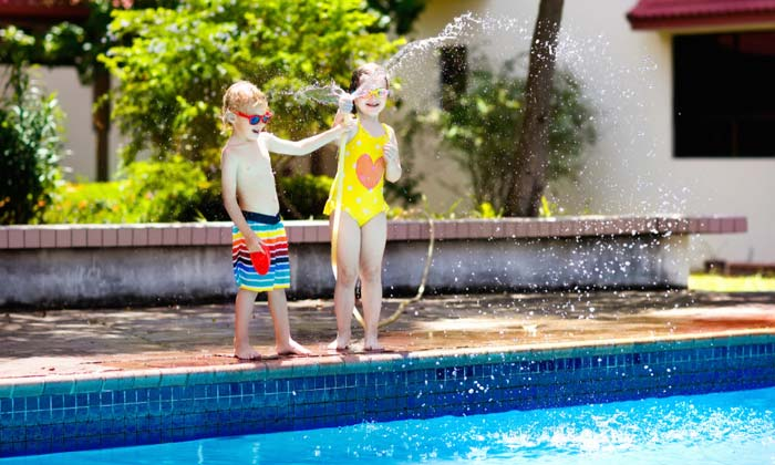 two young kids playing with water hose by pool edge