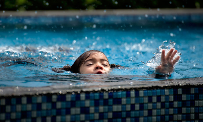 young child about to drown in swimming pool
