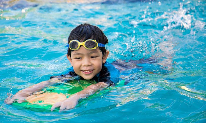 young goggle boy swimming with kick board