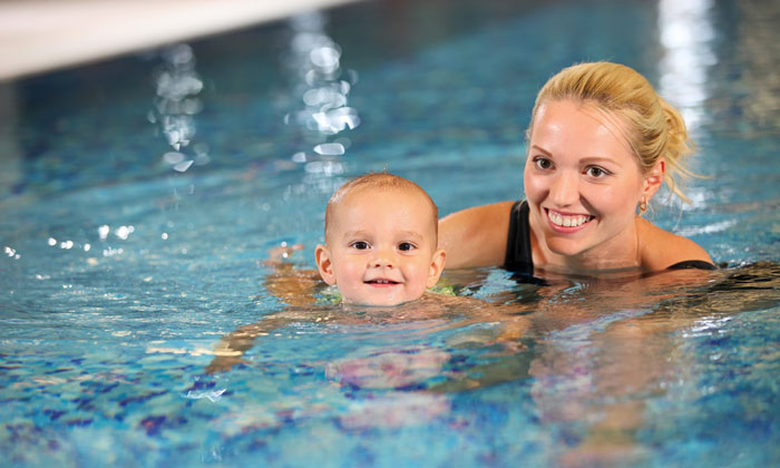 mother teaching very young child how to swim