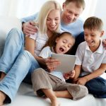 happy young family looking at tablet
