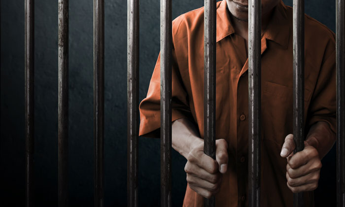 criminal behind jail cell bars
