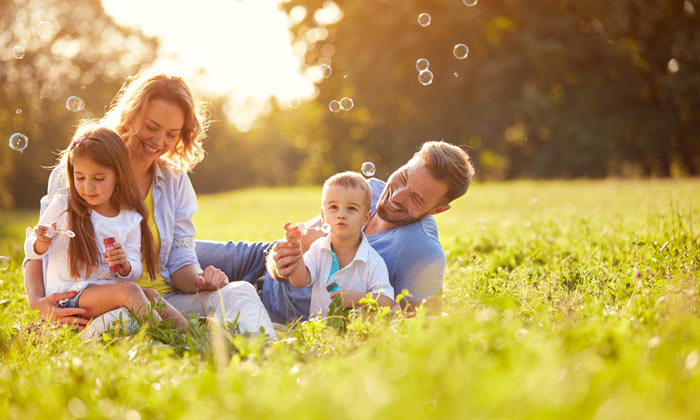 dad and mom with two young kids blowing bubbles in grass