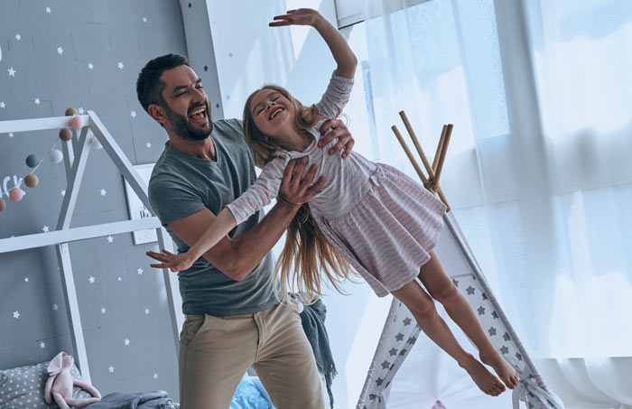 father holding young girl soaring in air