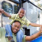 father with young son sitting on shoulders by camper