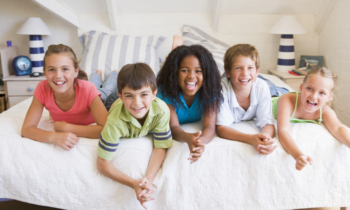 happy kids laying on bed laughing