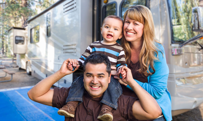 happy young couple with baby in front of camper
