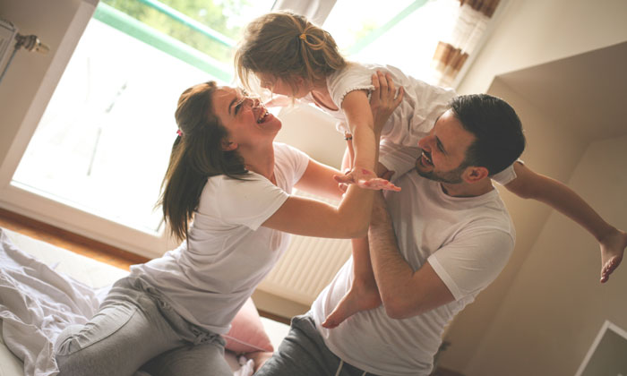 mother and father having fun at home with young daughter