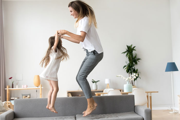 mother and little girl jumping on sofa