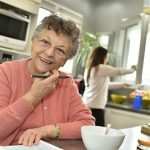 cheerful grandmother writing shopping list