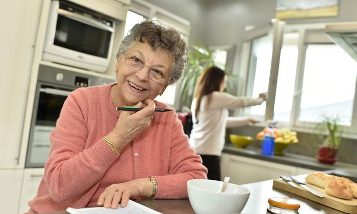 cheerful grandmother writing shopping list