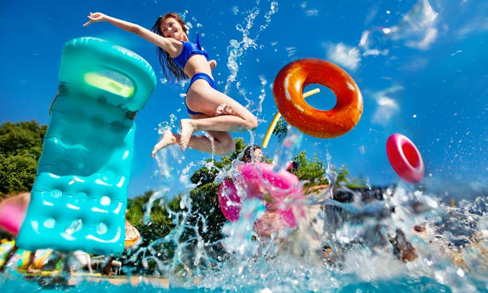 eager teens jumping into swimming pool