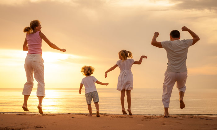 excited young family running in sand by ocean shore