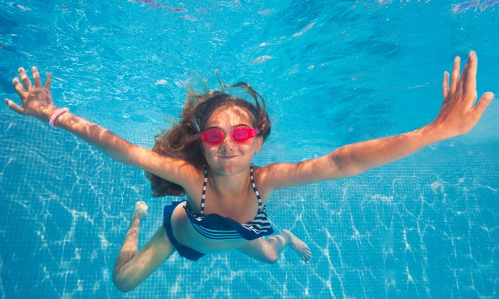 girl wearing goggles holding breath underwater