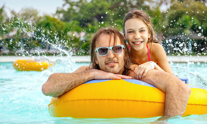 girl with father floating on pool water