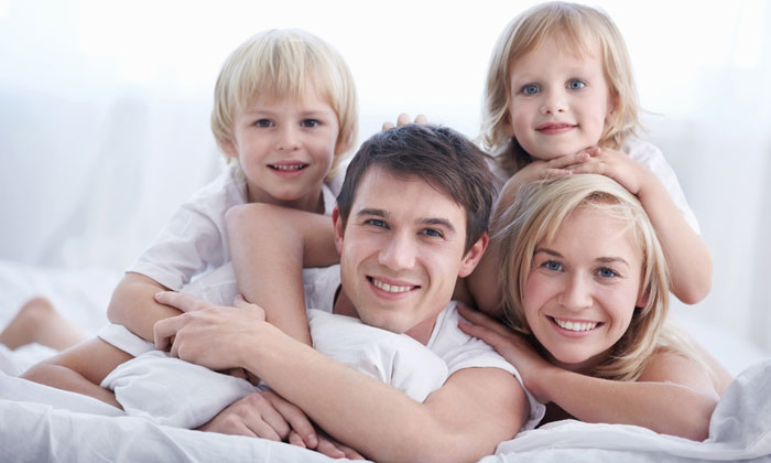 happy family with young kids resting on bed