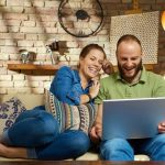 man and woman relaxing on couch laughing at computer