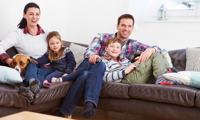 parents with kids sitting on sofas watching tv