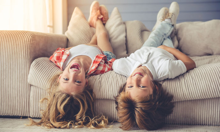 two silly kids upside down on sofa