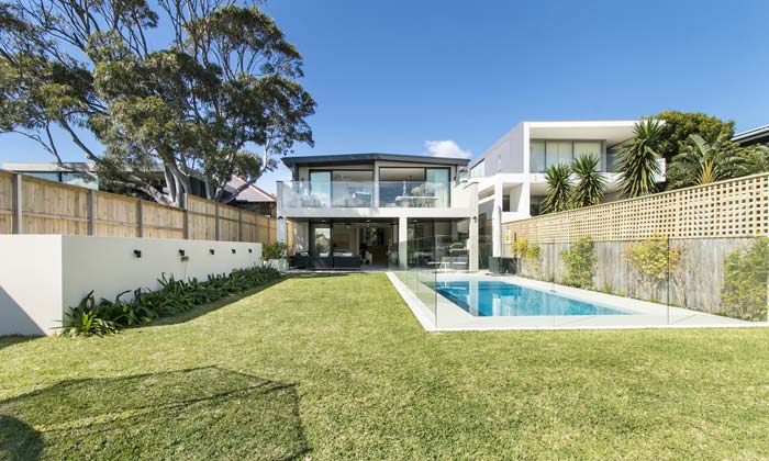 backyard swimming pool with glass wall fencing