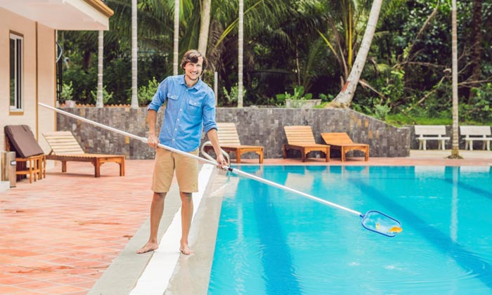 man removing leaves from pool
