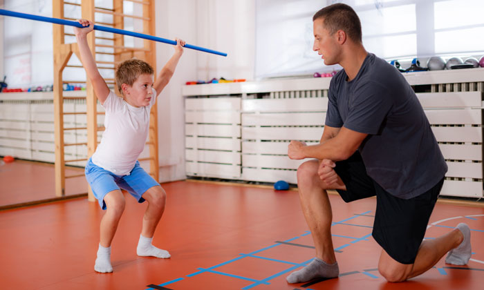 fitness instructor guiding young weight lifter