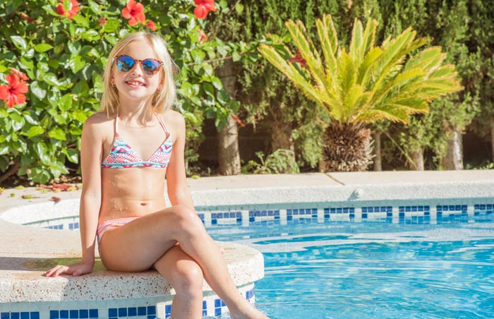 smiling young girl sitting by pool and bushes