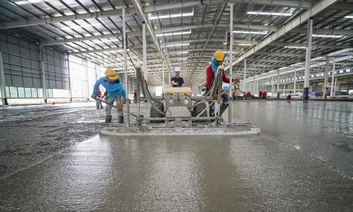 concrete workers making floor in warehouse