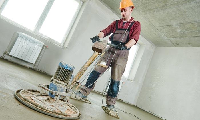 worker flattening fresh concrete floor