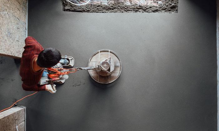 worker smoothening fresh concrete flooring